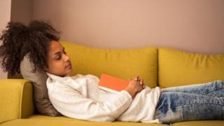 فتاة نائمة وهي تمسك بكتاب