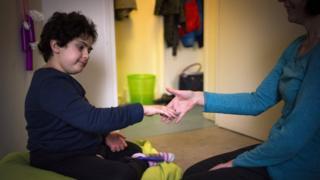 Một tình nguyện viên chơi với một trẻ tự kỷ tám tuổi ở trung tâm cho trẻ tự kỷ Lud'Eveil ở Paris, Pháp.