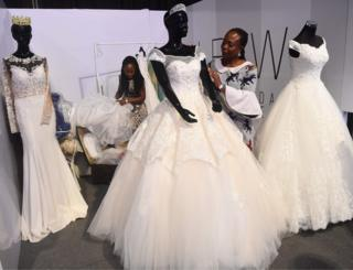 Employess of La Viva Bridal Concepts present wedding dresses during the Lagos Bridal Fashion Week in Lagos on May 4, 2018.