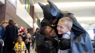 Lenny Robinson dressed as Batman cuddles two boys. Date unknown