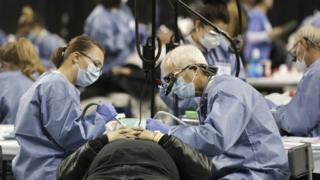 A patient receives free dental care at a charity clinic in Seattle