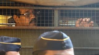 Mustafa Dossa sits inside a police van as he leaves from Arthur Road Jail for a special court in Mumbai (16 June 2017)