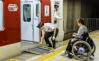 A wheelchair user boarding a train in Japan. A train worker is putting the ramp out for him.