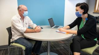Therapist seeing patient, both wearing masks