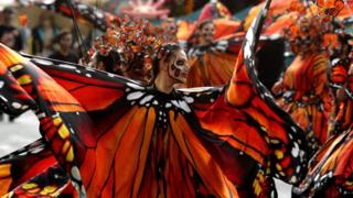 Women dressed as butterflies dance during the parade