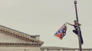 Bree Newsome takes down the Confederate Flag from a pole at the Statehouse in Columbia, South Carolina, June 27, 2015.
