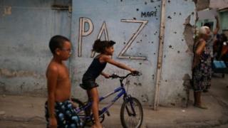 Crianças brincam diante de muro cravejado de tiros
