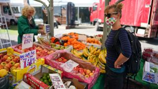 A woman buys produce from a market stall in York - 28 May 2020