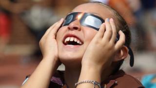 Imagem mostra menina usando óculos especiais para observar eclipse do sol