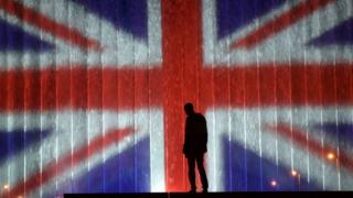 A man stands in front of a fountain illuminated with the colours of the United Kingdom flag on May 23, 2017, in Zagreb,