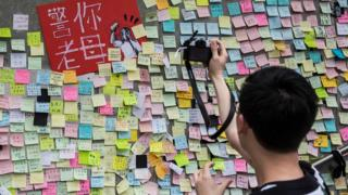 A man taking photographs of artwork and messages in support of protesters opposed to a China extradition law