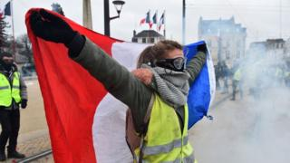 """A protester holds a French flag during an anti-government demonstration called by the """"Yellow Vest"""" (Gilets Jaunes) movement on January 12, 2019, in Le Mans, western France"""