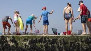Families fish for crabs from a sea wall in Margate.