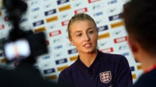 Leah Williamson being interviewed in front of a camera wearing an England sports jacket