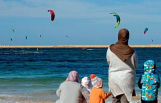 in_pictures Women and children watch a kite surfing tournament.