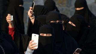 نساء سعوديات يلوحن بأجهزة المحمول