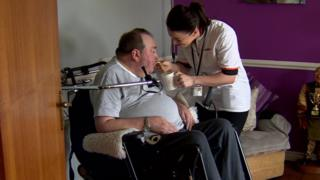 Carer Charlene McCoy gives a cup of tea to her patient Martin Harney