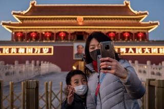A woman and a boy wearing protective masks take a selfie in front of a portrait of late communist leader Mao Zedong at Tiananmen Gate in Beijing.