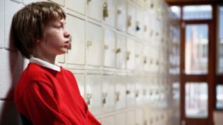 Boy sitting by school lockers