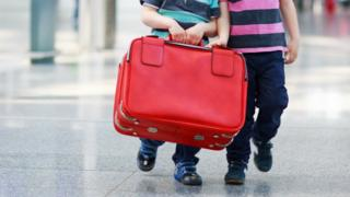 Boys carrying a suitcase