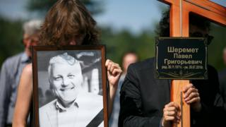 Relatives hold a portrait of killed journalist Pavel Sheremet and a cross during his funeral at a cemetery in Minsk, Belarus, Saturday, 23 July 2016.