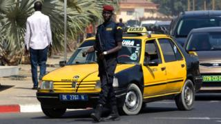 A Senegalese police officer stands guard outside a hotel in Dakar