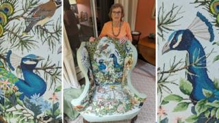 Nanny Pat with the chair that has propelled her to fame - it is an armchair with wildlife including peacocks and other birds and animals depicted on it.