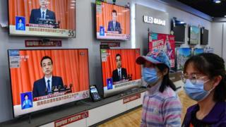 Los compradores pasan junto a una transmisión del primer ministro chino, Li Keqiang, pronunciando su discurso en la apertura de la APN