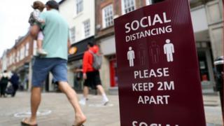 A man walking past a social distancing sign