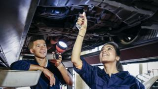 Two student mechanics repairing car
