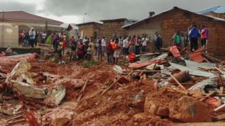 Residentes de la capital de Sierra Leona, Freetown, observan los destrozos causados por el deslave el 14 de agosto.