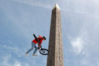 A member of France's BMX team shows off their skills at Place de la Concorde in Paris