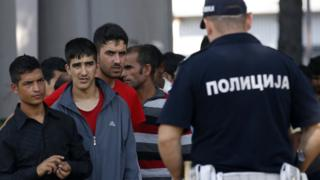 Serbian policeman/migrants at Sid transit camp, Serbia, 15 Sep 16