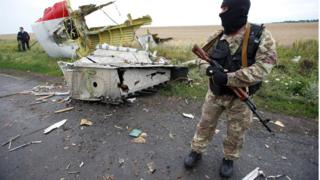 A pro-Russian separatist stands at the crash site of Malaysia Airlines flight MH17