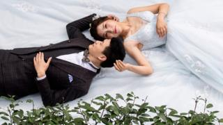 Bride and groom lying in a park