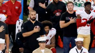 San Francisco 49ers quarterback Colin Kaepernick, middle, kneels during the national anthem before the team's NFL preseason football game against the San Diego Chargers, Thursday, Sept. 1, 2016, in San Diego