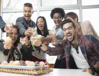 Ofiste kek yiyen çalışanlar.
