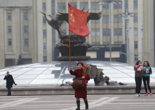 Aynı kentte yaşlı bir komünist kadın ise 8 Mart'ı tek başına, elinde Sovyetler Birliği bayrağıyla kutladı.