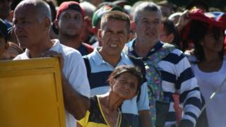 People wait to cross the Colombian-Venezuelan border over the partially opened Simon Bolivar international bridge