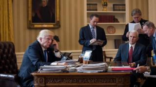 Donald Trump, seated at the desk of the Oval Office, speaks on the phone, surrounded by his chief of staff Reince Preibus, VP Mike Pence, strategist Steve Bannon, and press secretary Sean Spicer
