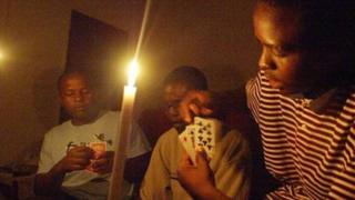 A family plays cards while candles are lit in Harare. File photo