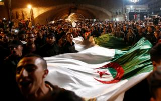 """People carry a national flag as they celebrate on the streets after Algeria""""s President Abdelaziz Bouteflika has submitted his resignation, in Algiers, Algeria, 2 April 2019."""