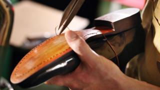 Shoemaker sewing a shoe.