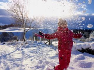 Child throwing snow in air near Lanark.