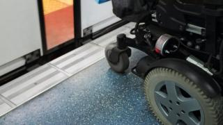 Wheelchair on a platform in front of a train with doors partially opened