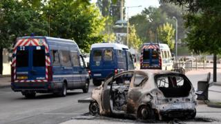 Police vehicles near a burnt car in Dijon