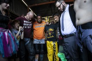 Members of a wrestling community are seen in prayer with their arms around each other.