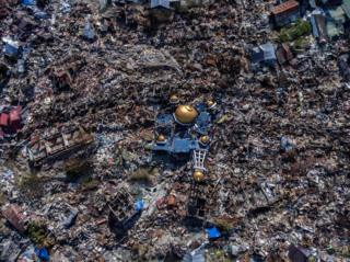Aerial view of a collapsed mosque amid rubble in
