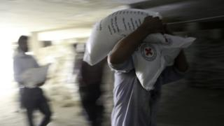 People unload supplies from a Syrian Arab Red Crescent (SARC) truck in the rebel-held town of Douma