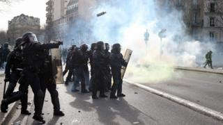 "Police officers throw tear gas to protesters during the 13th consecutive Saturday demonstration called by the ""Yellow Vests"""
